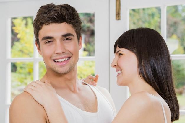 若いカップルの笑顔とリビングルームでお互いを抱きしめる