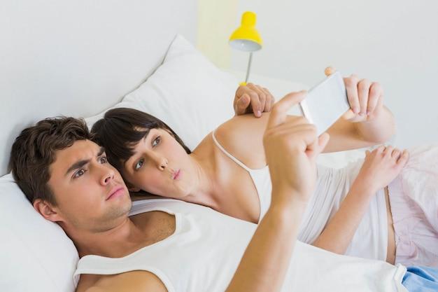 カップルはベッドに横たわって、寝室で携帯電話を見て