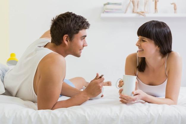 ベッドに横たわって、寝室で朝食を持っている若いカップル