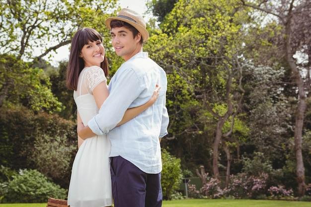 庭でお互いを受け入れて若いカップルの肖像画