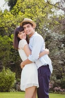 庭でお互いを抱きしめる若いカップルの肖像画