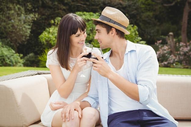 若いカップルがソファーに座っていると庭でワイングラスを乾杯