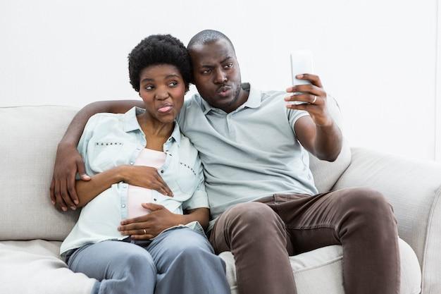 Беременная пара, принимая селфи на мобильный телефон у себя дома