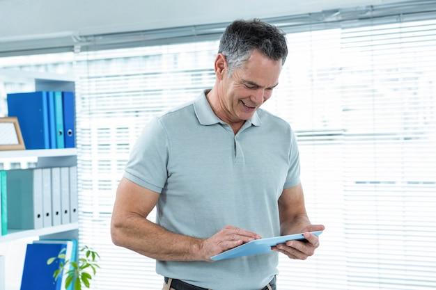 オフィスのオフィスでデジタルタブレットを使用して幸せな男