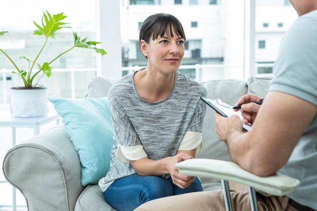 クリニックのセラピストと彼のメモを書くセラピストに相談する女性