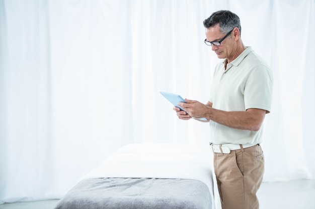 Физиотерапевт с использованием цифрового планшета в своей клинике