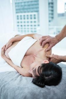 Беременная женщина получает массаж спины от массажиста в санатории