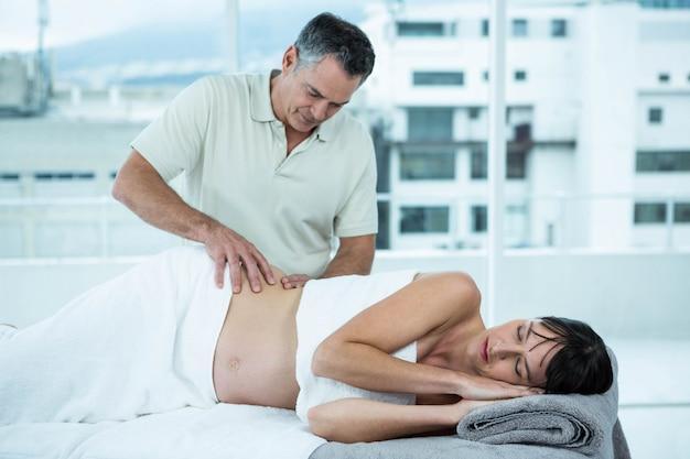 ヘルススパでマッサージ師から背中のマッサージを受ける妊娠中の女性