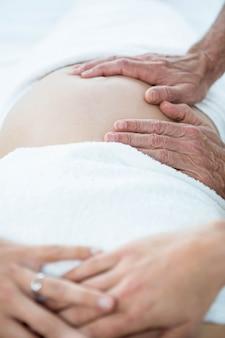 健康スパでマッサージ師から胃マッサージを受ける妊娠中の女性