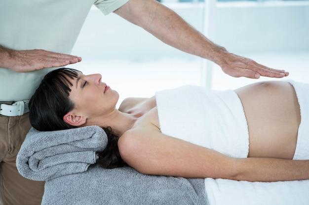ヘルススパでマッサージ師からマッサージを受ける妊娠中の女性