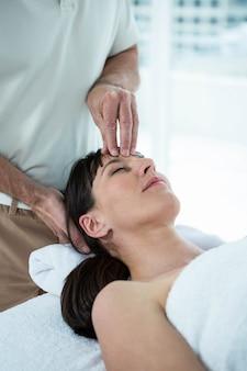 ヘルススパでマッサージ師から顔のマッサージを受けている妊娠中の女性