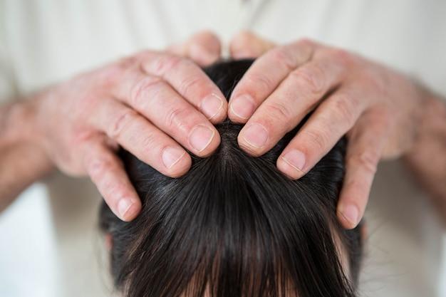 ヘルススパでマッサージ師からヘッドマッサージを受ける女性のクローズアップ