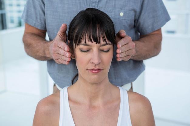 ヘルススパでマッサージ師からヘッドマッサージを受ける妊娠中の女性