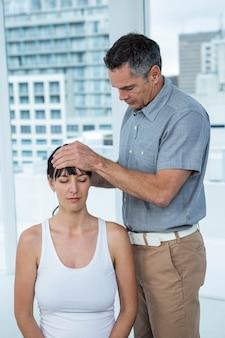 Беременная женщина получает массаж головы от массажиста в санатории