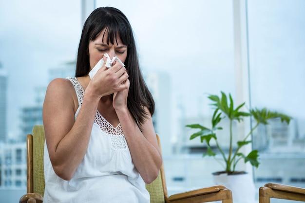 Беременная женщина вытирает нос в домашних условиях