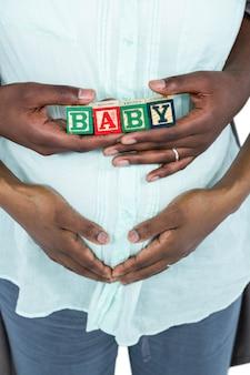 Беременная женщина с кубиками на животе и муж, обнимающий сзади