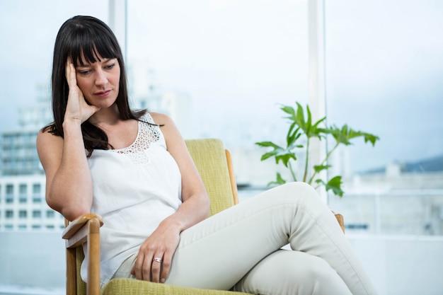 妊娠中の女性が自宅で頭痛で座っています。