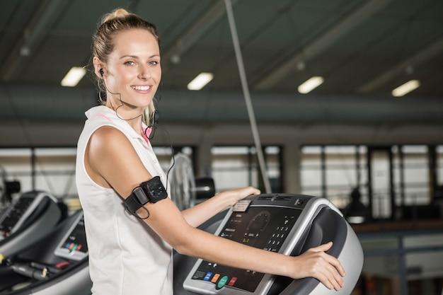 Женщина занимается на беговой дорожке в тренажерном зале