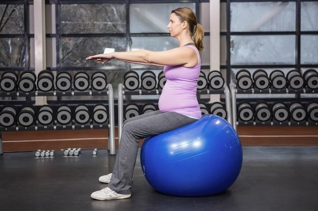 Определяется женщина, упражнения на фитнес-мяч в тренажерном зале
