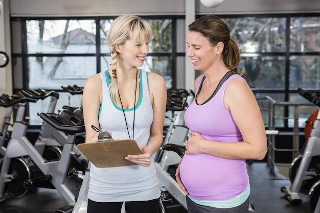 Улыбающийся тренер, показывая беременной женщины в тренажерном зале