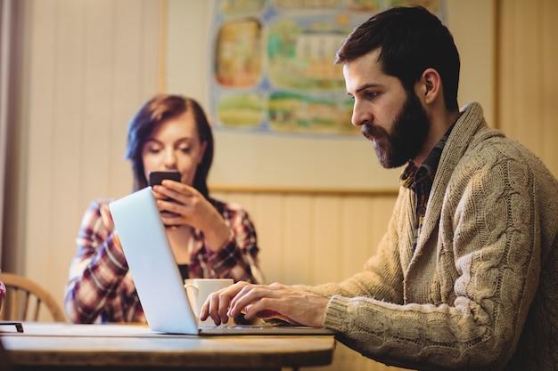 ノートパソコンと携帯電話を使用してカップル