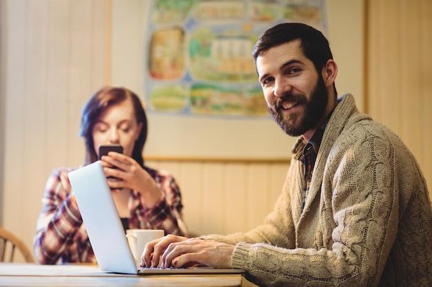 Пара, используя ноутбук и мобильный телефон