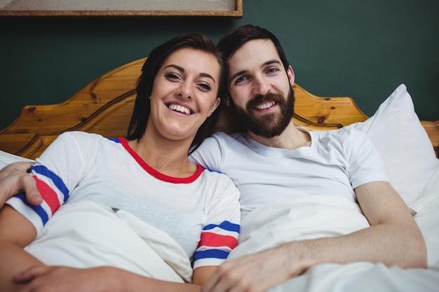 一緒にベッドに横たわっているカップルの肖像画