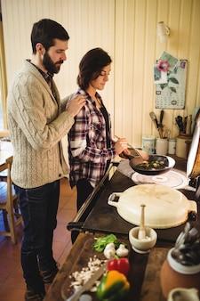 キッチンで一緒に食べ物を準備するカップル