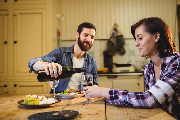 Мужчина наливает вино в бокал женщине