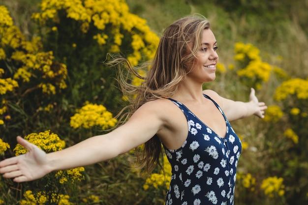 草原に広げられた腕によって立っている女性
