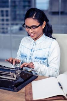 アジアの女性のオフィスでのタイプライター