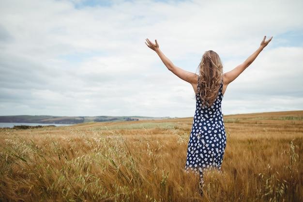 Женщина вид сзади, стоя с вытянутыми руками