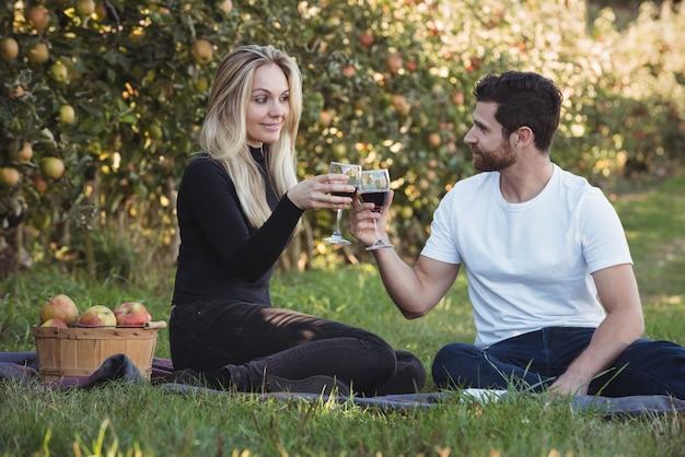 リンゴ園でワインのグラスを乾杯カップル
