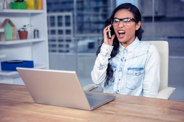 アジアの女性がオフィスで電話で叫んで