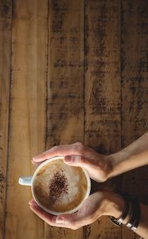 コーヒーカップを保持している女性のクローズアップ