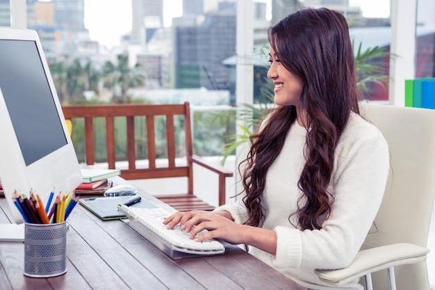 オフィスのコンピューターを使用して笑顔のアジア女性