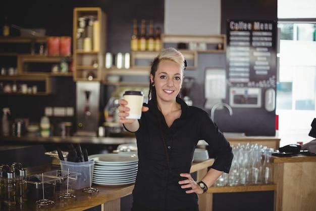 使い捨てのコーヒーカップで立っているウェイトレスの肖像画