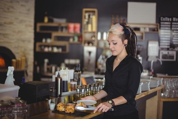 Официантка, обслуживающая кекс в тарелке у стойки