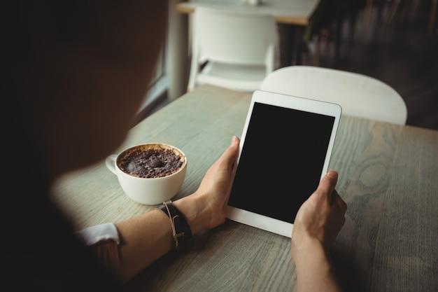 Женщина используя цифровую таблетку пока имеющ чашку кофе