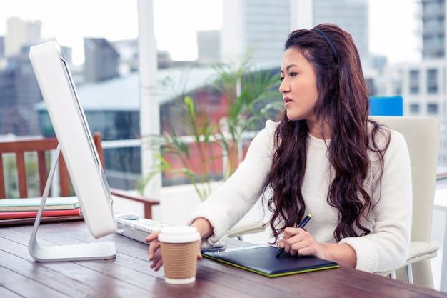 デジタルボードとオフィスでコンピューターを使用してアジアの女性に焦点を当ててください。