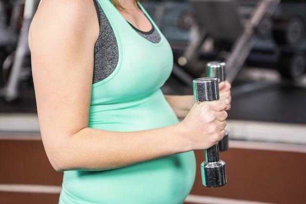 Средняя часть беременной женщины, держащей гантели в тренажерном зале