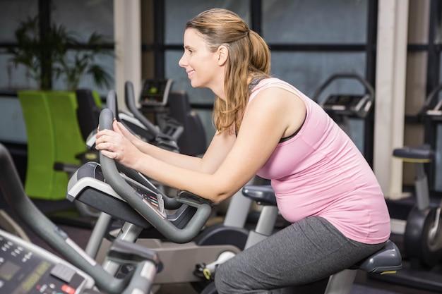 Улыбающаяся беременная женщина, сидящая на велотренажере в спортзале