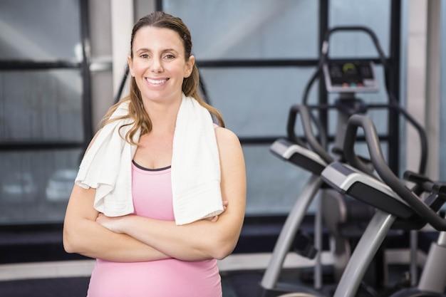 Улыбающаяся беременная женщина, стоящая со скрещенными руками в тренажерном зале