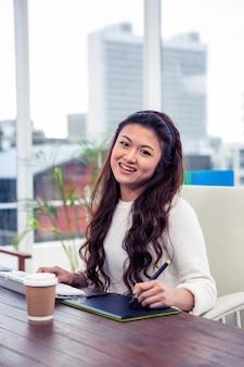 デジタルボードとオフィスでコンピューターを使用して笑顔のアジア女性