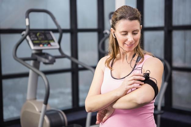 Беременная женщина слушает музыку в тренажерном зале