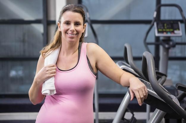 Усмехаясь беременная женщина стоя рядом с велотренажером на спортзале