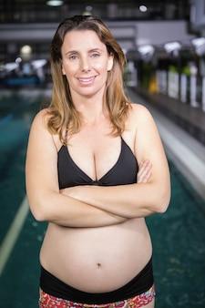 Улыбающаяся беременная женщина, стоящая рядом с бассейном в центре досуга