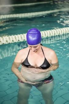 Беременная женщина, стоящая в бассейне и касающаяся ее живота в центре досуга