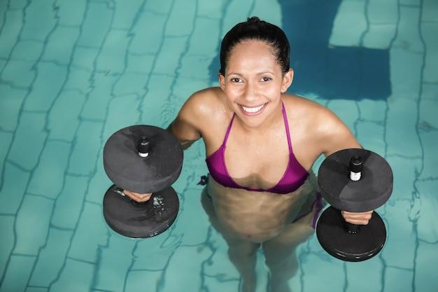 レジャーセンターで重みを持つプールで運動幸せな妊娠中の女性