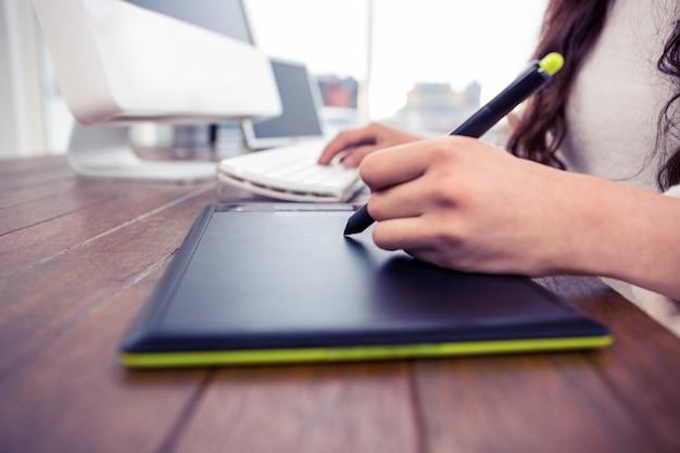 デジタルボードとコンピューターのキーボードを使用してオフィスで女性の手